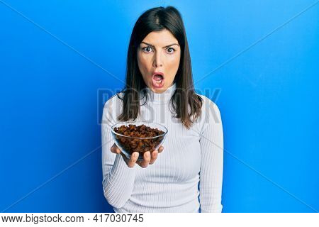 Young hispanic woman holding raisins bowl scared and amazed with open mouth for surprise, disbelief face