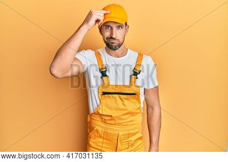 Young handsome man wearing handyman uniform over yellow background worried and stressed about a problem with hand on forehead, nervous and anxious for crisis