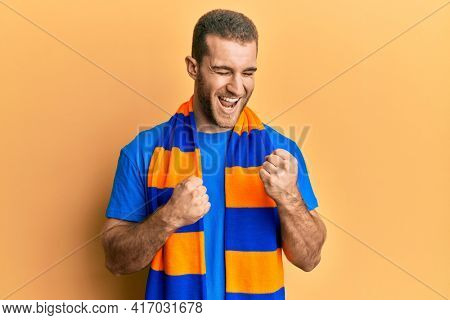Young caucasian man football hooligan cheering game celebrating surprised and amazed for success with arms raised and eyes closed