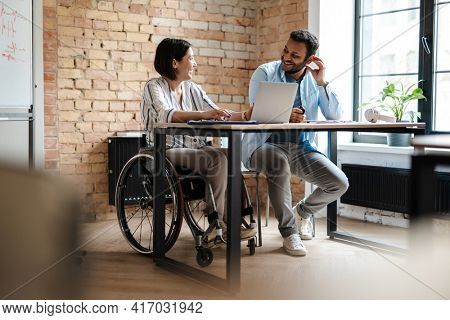 Multiracial young two colleagues smiling while working with laptop in office