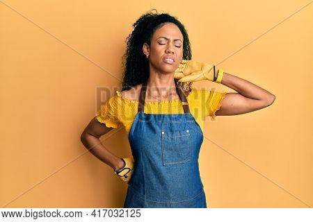 Middle age african american woman wearing professional apron suffering of neck ache injury, touching neck with hand, muscular pain