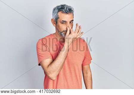Handsome middle age man with grey hair wearing casual t shirt smelling something stinky and disgusting, intolerable smell, holding breath with fingers on nose. bad smell