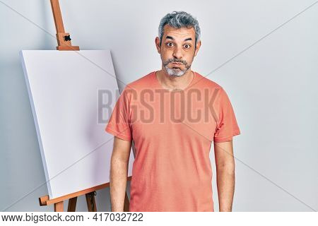 Handsome middle age man with grey hair standing by painter easel stand puffing cheeks with funny face. mouth inflated with air, crazy expression.