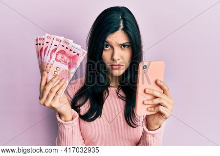 Young hispanic woman using smartphone holding chinese yuan banknotes skeptic and nervous, frowning upset because of problem. negative person.