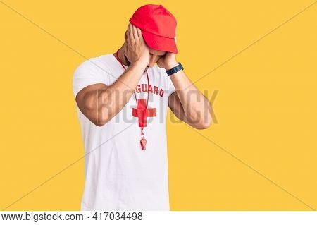Young caucasian man wearing lifeguard t shirt holding whistle suffering from headache desperate and stressed because pain and migraine. hands on head.