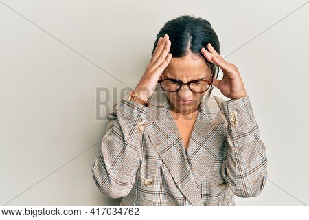 Young brunette woman wearing business jacket and glasses suffering from headache desperate and stressed because pain and migraine. hands on head.