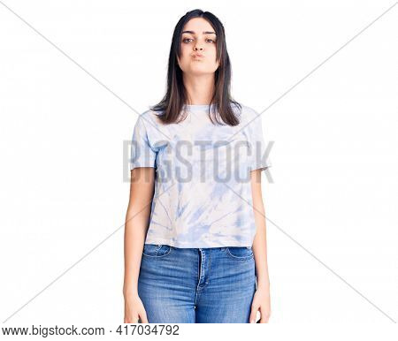 Young beautiful girl wearing casual t shirt puffing cheeks with funny face. mouth inflated with air, crazy expression.