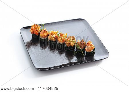 Gunkan Sushi - Gunkan Maki Sushi with Seafood and Spicy Sauce. Sushi with Rice inside and wrapped nori seaweed around. Delicious Gunkan Sushi on black slate plate. Isolated on white background