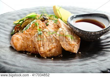 Teppanyaki Style Salmon - Grilled Salmon Fillet with Soy Sauce and Vegetables. Japanese Teppanyaki Salmon Steak garnished with lemon and green beans leaf. Black asian plate close up view