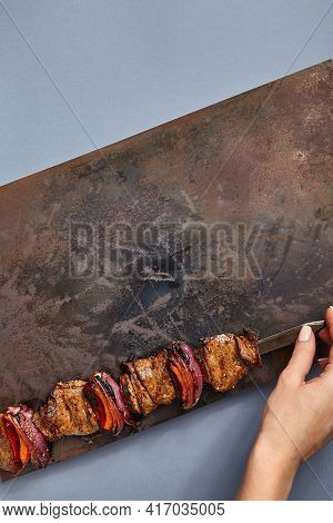 BBQ Skewered Meat on Rusted Metal Tray. Minimal barbecue top view with rusty metal texture on dark blue table. Woman hand hold metal skewer