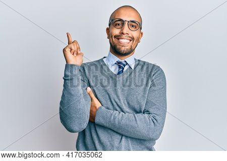 Hispanic adult man wearing glasses and business style with a big smile on face, pointing with hand and finger to the side looking at the camera.