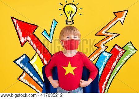 Superhero Child Playing Indoor. Portrait Of Super Hero Kid Against Yellow Paper Background. Stop Cor