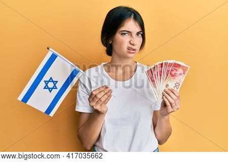 Young caucasian woman holding israel flag and shekels banknotes skeptic and nervous, frowning upset because of problem. negative person.