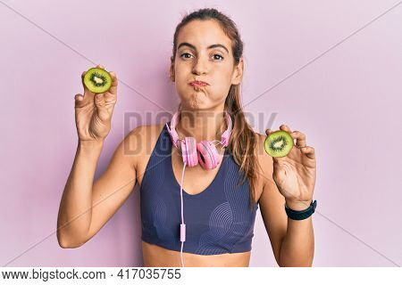 Young beautiful woman wearing gym clothes holding slice of kiwi puffing cheeks with funny face. mouth inflated with air, catching air.