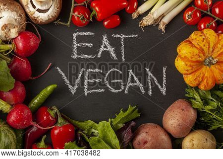 A Medley Of Raw Vegetables Around A Black Board. In The Middle There Is A Text That Says Eat Vegan.