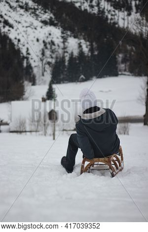 Teenager Sitting On A Wooden Vintage Sled And Trying To Brake A Fast Wooden Sled. Fooling Around On