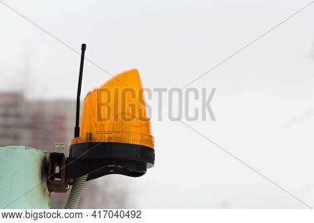 Close-up Of A Yellow Beacon With An Antenna For Transmitting An Alarm. Signal Lamp On A Metal Pole A
