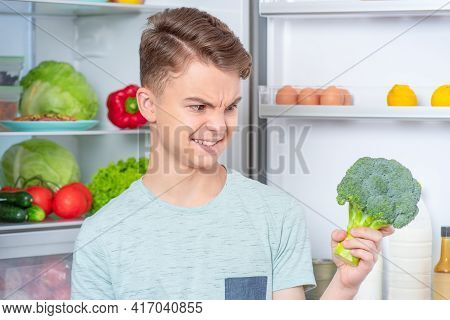 Portrait Of Young Teen Boy Holding Fresh Green Broccoli While Standing Near Open Fridge In Kitchen A