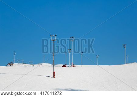 Ski Resort, Snow Slope, Trail With Artificial Lighting Towers. Mountain Slope For Skiing And Snowboa