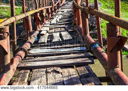 Old Footbridge With Balustrade And Broken Wooden Planks