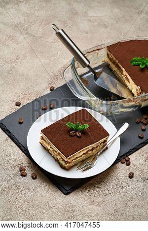 Traditional Italian Tiramisu Dessert In Glass Baking Dish And Portion On Grey Concrete Background