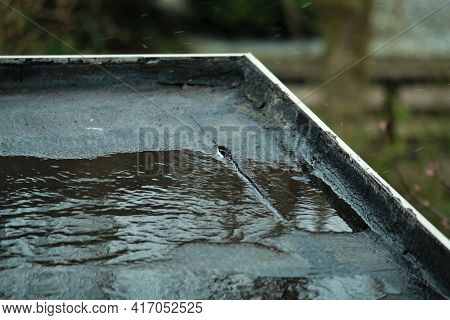 Light Rain On A Black Flat Roof With A Small Leak