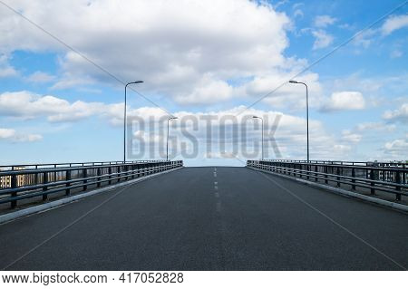 Asphalt Road With A Pedestrian Safety Fence Against A Blue Sky With Clouds. Urban Infrastructure, Ro