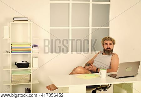 Handsome Man Using Laptop At Home. Self Quarantine Routine. Serene Barefoot Guy Resting, Daydreaming