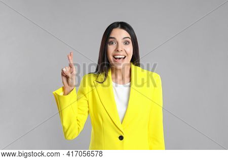 Woman With Crossed Fingers On Grey Background. Superstition Concept