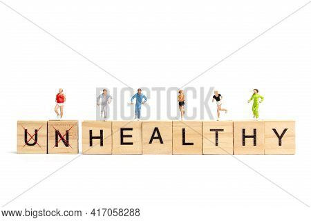 Miniature People Running On Wooden Letter Block On White Background