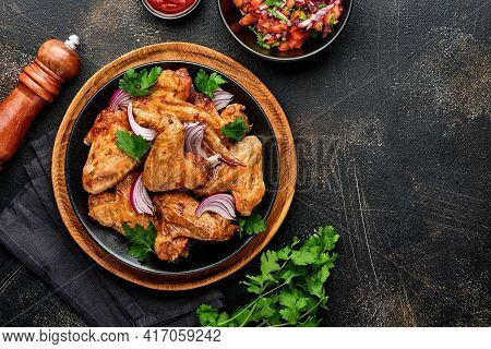 Grilled Chicken Wings Or Roasted Bbq With And Tomato Salsa Sauce On A Black Plate. Top View With Cop