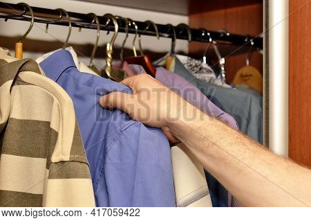 Change Of Seasons Male Hand Takes Off Blue Shirt From Hanger
