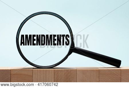Cubes On A Light Blue Wooden Background. On Them A Magnifying Glass With The Word Amendments