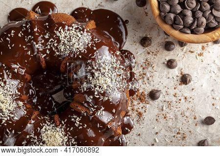 Flat Lay Image Of A Chocolate Cake With Melted  Pudding Icing And Chocolate Chips In A Bowl In The B