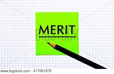 There Is A Green Sticker With The Text Merit And A Black Pencil On The Checkered Paper.