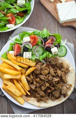 Greek Gyros With Fries And Salad On A Plate.