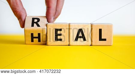 Real Heal Symbol. Doctor Turns A Wooden Cube With Words 'real Heal'. Beautiful Yellow Table, White B