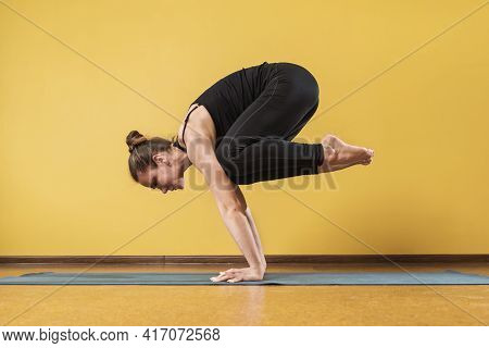 Woman Practicing Yoga, Doing Bakasana Exercise, Crane Pose, Sportswoman Exercising On A Mat Near The
