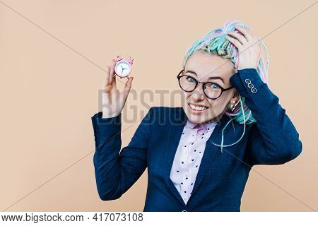 Business Lady Is Holding Pink Alarm Clock On Beige Background. Young Woman With Colored Dreadlocks,
