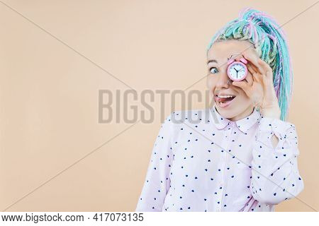 Surprised Girl Freelancer Is Holding Pink Alarm Clock. Young Woman With Colored Dreadlocks Is Shocke