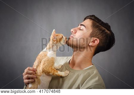 Side View Of Young Handsome Man With Closed Eyes Holding And Kissing Muzzle Cute Devon Rex Cat On Da
