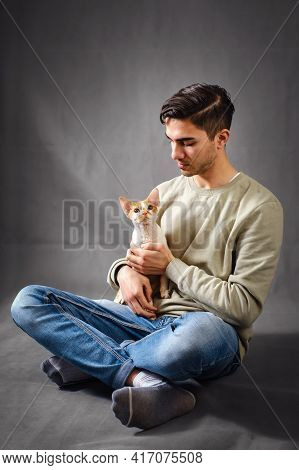 Young Handsome Man Holding Cute Devon Rex Cat And Sitting On Dark Gray Background With Copy Space. V