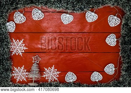 Christmas Composition On Red Wooden Board With Christmas Garland And Decorations. Creative Compositi
