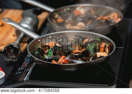 The Chef Prepares A Seafood Dish. Frying Pan With Seafood And Lemon And Basil. Shrimp Squid And Muss