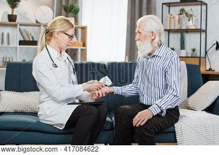 Middle Aged Practitioner Visiting Sick Elderly Man Patient At Home. Young Blond Woman Doctor Measuri
