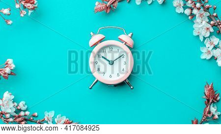 Spring Border, Spring Blossom And April Floral Nature With Alarm Clock On Blue Background. Branches