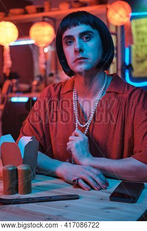 Portrait Of Young Transgender Looking At Camera While Sitting At The Table In Nightclub