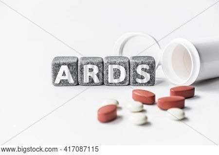 Word Ards Is Made Of Stone Cubes On A White Background With Pills. Medical Concept Of Treatment, Pre