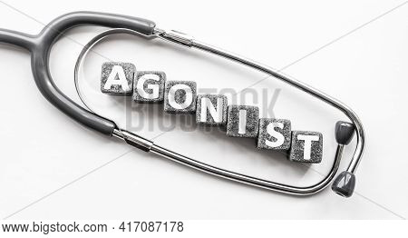 Stone Block Form Word Agonist With Stethoscope. White Background. Medical Concept. Substance, Trigge