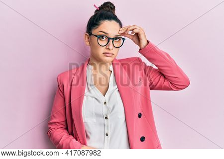 Beautiful middle eastern woman wearing business jacket and glasses worried and stressed about a problem with hand on forehead, nervous and anxious for crisis